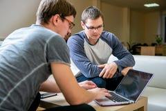 两青年人在办公室谈论项目 紧挨着坐在桌上,他们中的一个告诉其他关于喂 免版税库存图片