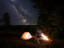 两青年人坐日志近的灼烧的火在帐篷附近在满天星斗的天空上的强有力的冷杉木下 免版税库存照片
