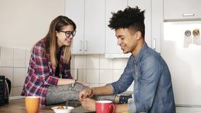 两青年人逗人喜爱的夫妇爱的有下降交谈,坐在一个轻松的厨房,享受他们的膳食 股票视频