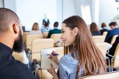 两青年人写和谈话在业务会议 免版税图库摄影