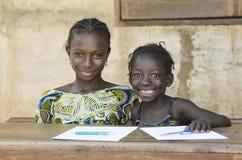 两非洲种族儿童微笑的学习在学校Envi 库存照片