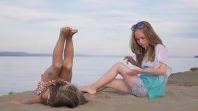 两面少年儿童坐海滩 股票视频
