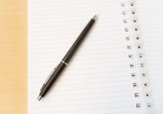 两页打开有黑笔的笔记本与Id的木表面上 库存照片