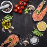 两鲑鱼排、黄油、盐和胡椒、柠檬和西红柿,大蒜,文本的,在木土气backgrou的框架草本地方 免版税库存照片