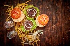 两鲜美烤家做了汉堡用牛肉、蕃茄、葱和莴苣 库存照片