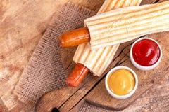 两鲜美烤法国热狗用芥末和番茄酱 库存照片