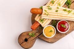 两鲜美烤法国热狗用芥末和番茄酱 库存图片