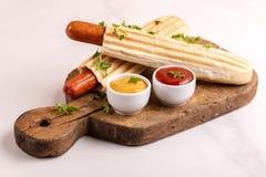 两鲜美烤法国热狗用芥末和番茄酱 图库摄影