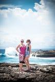两年轻和岩石的性感的妇女在狂放的海洋附近 风暴,飞溅巨大的波浪来和 热带海岛努沙 库存图片