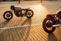 两黑和银色葡萄酒习惯摩托车caferacers 免版税库存照片