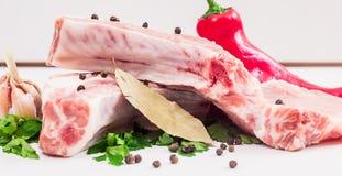 两水多的肉片在骨头的用红辣椒荚,荷兰芹和大蒜和月桂叶在一张木桌上说谎 图库摄影