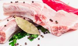 两水多的肉片在骨头的用红辣椒荚,荷兰芹和大蒜和月桂叶在白色背景说谎 免版税库存图片