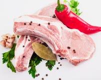 两水多的肉片在骨头的用红辣椒荚,荷兰芹和大蒜和月桂叶在白色背景说谎 免版税库存照片
