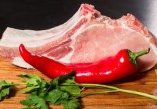 两水多的肉片在骨头的用红辣椒荚,荷兰芹和大蒜在一张木桌上说谎 免版税库存图片