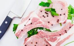 两水多的肉片在骨头的用胡椒和刀子在白色背景说谎 库存照片