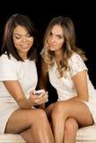 两件妇女白色礼服坐电话一神色 免版税库存照片