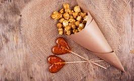 两以心脏的形式棒棒糖和一个纸袋在木背景的焦糖玉米花 免版税库存照片