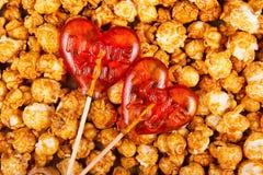 两以心脏的形式棒棒糖在焦糖玉米花背景  库存照片