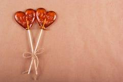 两以心脏的形式棒棒糖在纸背景 免版税库存照片