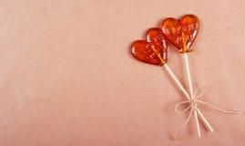 两以心脏的形式棒棒糖在褐色背景回收了纸 图库摄影