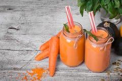 两份桔子圆滑的人饮料一张顶视图在巨大的金属螺盖玻璃瓶的用成熟裁减红萝卜和绿色植物灰色背景的 库存照片