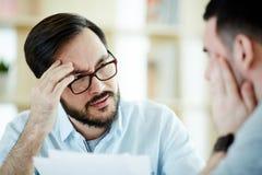 两麻烦了同事谈论工作在会议 免版税库存图片
