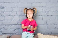 两年的一个小滑稽的女孩坐长沙发,听到在她的头上把放的耳机的音乐 拿着一个智能手机 免版税库存图片