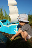 两年的男孩和有一个风帆的一艘自制船在岸 库存照片