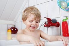 两年的逗人喜爱的矮小的小孩男孩获得乐趣通过采取浴我 库存图片