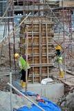两建筑工人制造的专栏模板 免版税库存照片