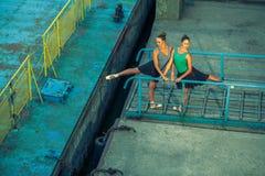 两年轻美好的双姐妹跳舞芭蕾在有芭蕾服装的城市 都市sync舞蹈 工业街道跳舞 与 免版税库存图片