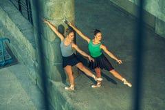两年轻美好的双姐妹跳舞芭蕾在有芭蕾服装的城市 都市sync舞蹈 工业街道跳舞 与 免版税库存照片
