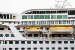 两黄色和在游轮的白色救生艇 库存图片