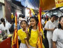 两黄色衬衣举行旗子的小女孩 图库摄影