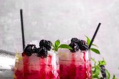 两份莓果饮料特写镜头用在灰色的薄菏弄脏了背景 饮料用酸柠檬、新鲜薄荷和甜点 库存照片
