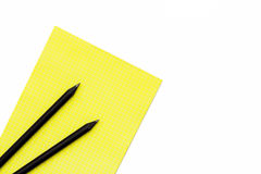 两黑铅笔和一个黄色笔记薄在白色背景 最小的概念工作场所在办公室 图库摄影