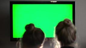 两年轻长发白肤金发的观看的绿色电视屏幕和笑 股票视频