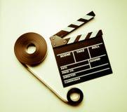 两35mm电影卷轴和clapperboard在葡萄酒上色作用 库存图片