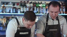 两barmanan工作和谈论某事在柜台在酒吧 免版税库存照片