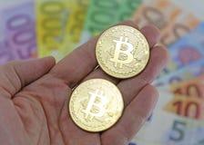 两goden BITCOIN和被弄脏的欧洲钞票在背景 免版税库存照片