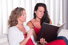 两siiting在长沙发的可爱的妇女谈论和注意 免版税库存照片