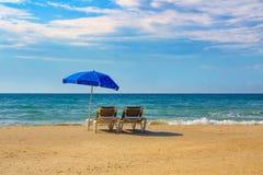 两sunbeds在海滩的一把伞下 库存图片