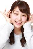 严密地听的少妇用在耳朵后的手 库存图片