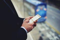 严密地男性成功的总经理键入在手机的电子邮件信件 免版税库存图片