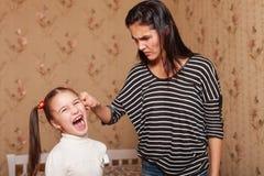 严密的母亲由耳朵拿着她的女儿 免版税库存图片