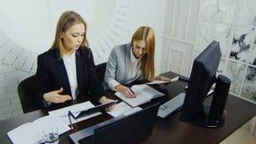严密的西装的两名年轻雇员检查责任在工作场所以回合为背景 影视素材