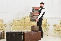 严密的面孔的强壮男子,典雅的搬运工运载堆葡萄酒手提箱 男管家和服务概念 有胡子的人和 免版税库存照片