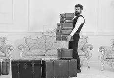 严密的面孔的强壮男子,典雅的搬运工运载堆葡萄酒手提箱 男管家和服务概念 有胡子的人和 免版税库存图片