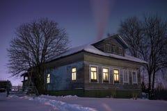 严寒的舒适老俄国村庄房子 冬天与雪,星,从熔炉的烟的夜风景和温暖 库存图片