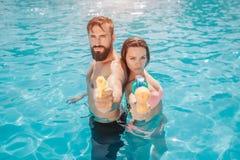 严肃和被集中的夫妇在游泳池和神色紧接站立在照相机 他们摆在 人和女孩举行 免版税库存照片